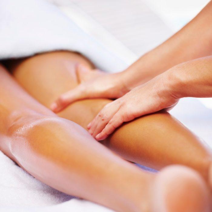 Closeup photo of a masseur giving lady a leg massage